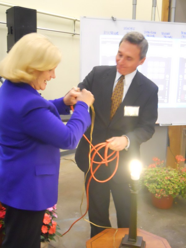 U.S. Rep. Chellie Pingree and SMCC President Ronald Cantor plug a light bulb into energy supplied by photovoltaic panels on the south side of the community college's new Sustainability and Energy Alternatives Center building Thursday morning.