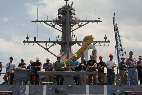 Employees at Bath Iron Works watch from an upper deck on an Aegis destroyer in 2009.