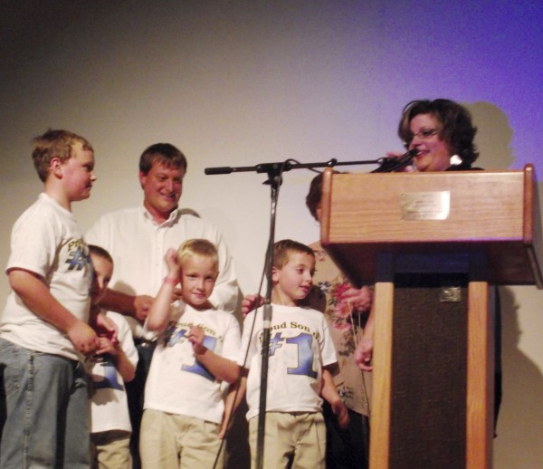 Alana Margeson, a grade 10-11 English teacher at Caribou High School who was named Maine's 2012 Teacher of the Year on Thursday, Sept. 15, 2011, is joined on stage by her husband, Erich, and their four children. Margeson was awarded the honor during a surprise all school assembly attended by more than 500 students, colleagues, family and friends.