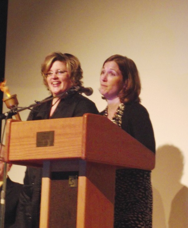 Alana Margeson (left) Maine's 2012 Teacher of the Year, holds up a torch passed to her by Shelly Moody (right), Maine's 2011 Teacher of the Year. The two women grew up together in Caribou. Margeson garnered the award during a special assembly at Caribou High School on Thursday, Sept. 15, 2011.