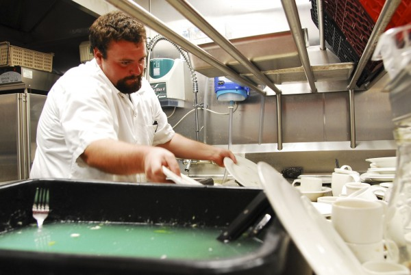"Maxwell Payne washes dishes after the lunch rush at the newly opened The Inn at Brunswick Station in Brunswick. He says he plans to work his way up into food prep and cooking. A –path many in tourism have taken. """"It depends on how fast you can learn, really,"""" he says."
