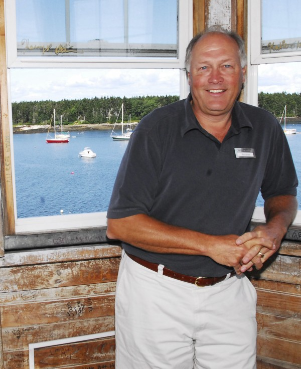 "Bob Smith, owner of the Sebasco Harbor Resort in Phippsburg, shows off the view from the lighthouse on the property in June. One of his titles is ""lighthouse keeper."""
