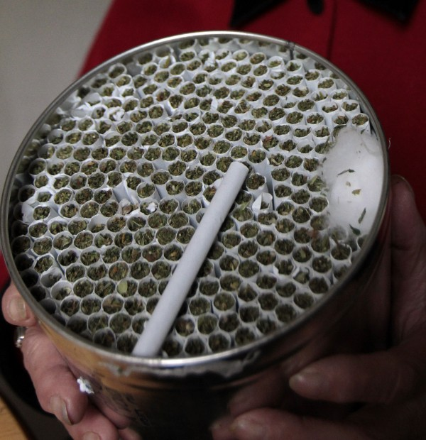 Elvy Musikka, 72, who suffers from glaucoma, shows the canister holding marijuana cigarettes she regularly receives from the U.S. Government in Eugene, Ore., Tuesday, Sept. 27, 2011.