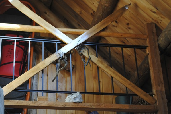 A pair of vintage cross country skis hangs from the railing in the main lodge at Little Lyford Pond Camps, an Appalachian Mountain Club facility.