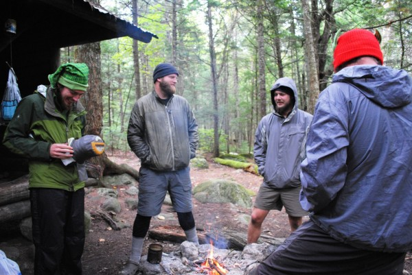 "An unidentified thru-hiker, Martin ""Giggle"" Lieb (from left), ""Mike D,"" Brian ""Calculator"" Snyder share a laugh over a warming fire at Hurd Brook lean-to on the Appalachian Trail, three miles south of Abol Bridge. After one more overnight, they'll fiinish their six-month thru-hike by hiking Katahdin."