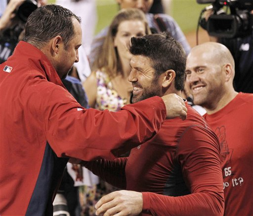 Boston Red Sox starting pitcher Tim Wakefield, left, is congratulated by teammates Jason Varitek, center, and Kevin Youkilis after recording his 200th career win in Boston's 18-6 win over the Toronto Blue Jays at Fenway Park in Boston on Tuesday night, Sept. 13, 2011.