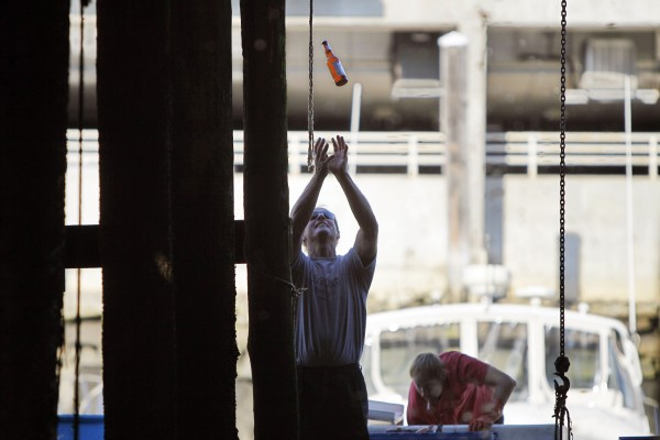 A fisherman reaches up to catch a beer after tying up at Widgery Wharf in Portland.
