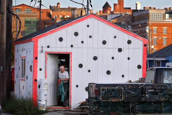David MacVane heads out to fish after a brief stop in his fishing shack on Widgery Wharf in Portland. The polka dot color scheme of his fishing shack echos the markings on of his lobster trap buoys.