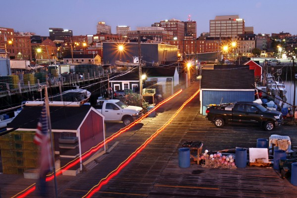 While most of Portland still sleeps, a delivery truck leaves a trail of light as it backs down Widgery Wharf to make an early-morning lobster pick up.