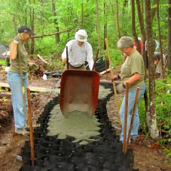 Friends of Acadia volunteers Becky Heden (left) of Bar Harbor and Freehold, N.J., and Kathleen Campbell of Leesburg, Fla., watch as another volunteer dumps a load of gravel into a honeycomb-like web that will be the foundation of a new connector