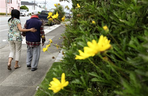 Shirley Rexrode, left, assists her father, Hsien-Wen Li, who is an Alzheimer's patient, with his daily walk, in San Francisco.