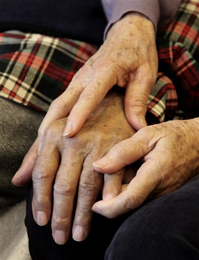 Shou-Mei Li holds the hand of her husband Hsien-Wen Li, who is an Alzheimer's patient, at their home in San Francisco. Dementia is poised to become a defining disease of a rapidly aging population -- and a budget-busting one for Medicare, Medicaid and families.