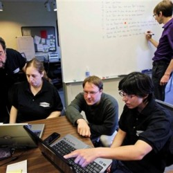 Aspiritech co-founder Moshe Weitzberg, standing left, works with employees, from left, Katie Levin, Rick Alexander and Jamie Specht, at the nonprofit enterprise that specializes in finding software bugs as they test a new program in Highland Park, Ill. Marc Lazar, Aspertech's autism specialist works in the background.
