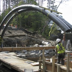 Workers maneuver a carbon fiber tube over the Little River in Belfast last year while installing a Bridge-in-Backpack.
