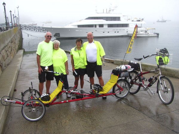 Lee Kayhart, far right, stands with his wife, Pat, as well as friends Bob and Terri Rohde on the Bar Harbor boat ramp on Saturday, Sept. 24, 2011, not long after completing a coast-to-coast bike ride. Lee Kayhart, of Addison, Vt., lost both arms in a farming accident more than 25 years ago but never let the loss stop him from achieving things, his wife said. The couple rode a 3-wheeled recumbent bike retrofitted to allow Lee Kayhart to shift gears, steer and brake with his prosthetic arm and hook. They said Sunday that they plan to fly back across the country this time, however.