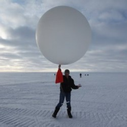 Atop roughly two miles of ice, technician Marie McLane launches a data-transmitting weather balloon at Summit Station, a remote research site.