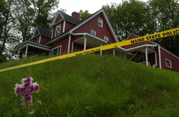 A cross stands erected in front of police tape at 173 Shore Road in Dexter in June 2011, one day after Steven Lake shot and killed his estranged wife Amy and their two children, Monica and Coty.
