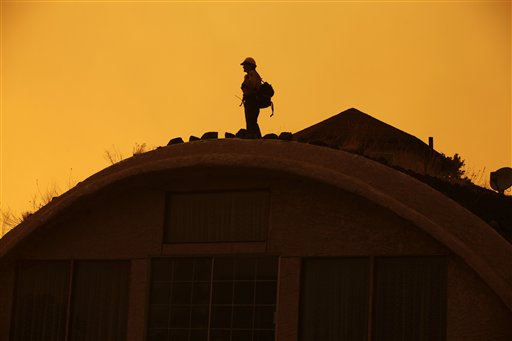 A firefighter keeps a lookout on the roof of a house as the Wallow fire approaches Eagar, Ariz., last June.