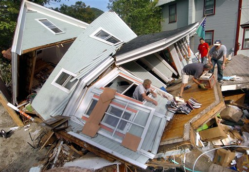 Brad Leathers, in window, and Ed Wissner remove items from the destroyed home of Jon Graham, right, after it was destroyed during Tropical Storm Irene in Rochester, Vt.