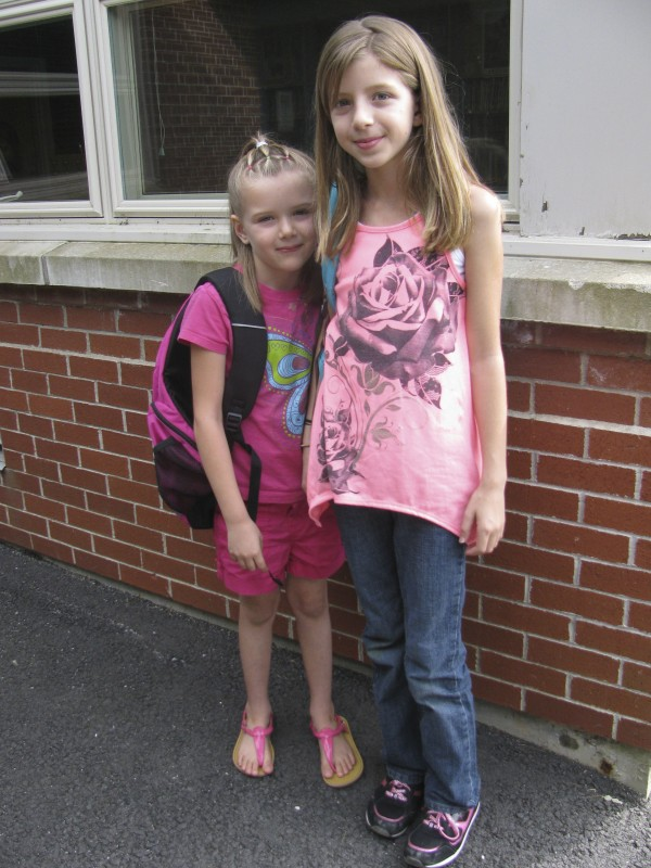"Sisters MacKenzie Rainey, 10, and Alyssa Rainey, 5, stand outside Frankfort Elementary School on Wednesday afternoon. It was the first day of kindergarten for Alyssa and the second day of fifth grade for MacKenzie, who said she is glad that the school — slated last spring to be closed for good in June — remained open. ""It's small, and better to make friends,"" she said."