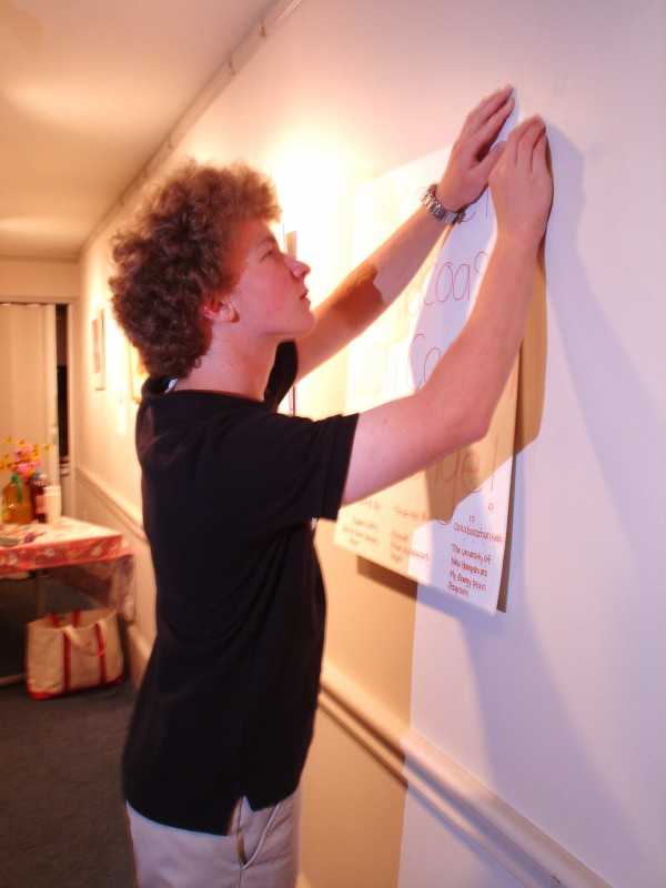 Matt Clark of Rockport puts up a poster as part of the Green Sneakers/Future Homeowners Community Carbon Challenge.