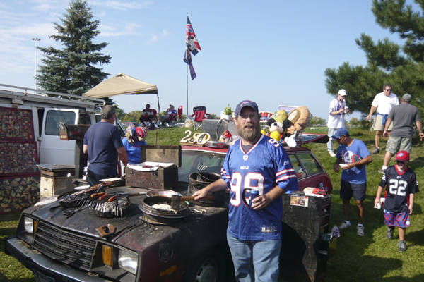 "Buffalo Bills super-fan Kenny Johnson with the 1980 Ford Pinto station wagon he has used as a grilling station for the past two decades. The Rochester, N.Y., resident drives his still-running Pinto to all home (and some away) games and cooks a wide range of dishes on its hood. Johnson's ""Pinto Tailgate,"" is a must stop for fans looking for fun and food. Over the years Johnson has treated fans to thousands of dollars worth of goodies."
