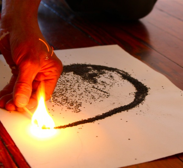 Mark Kelly of Belfast lights an arc of gunpowder Monday, Aug. 29, on the floor of the Aarhus Gallery in Belfast to show his fellow artists how he draws using gunpowder. Kelly's gunpowder drawings of a variety of birds will be on display through Oct. 2 at the gallery.