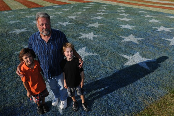 Buddy Patterson, center, along with his grandsons Scott Fahey, left, and James Fahey, right, stand on a painted American flag in Paterson's back yard in Holden on Tuesday, September 13, 2011. Patterson and his helpers sprayed paint on a   9,936 square foot section of lawn on Friday and Saturday, Sept. 9-10 to honor the 10th anniversary of 9/11. Patterson is in the process of closing on the home and moving to Florida.