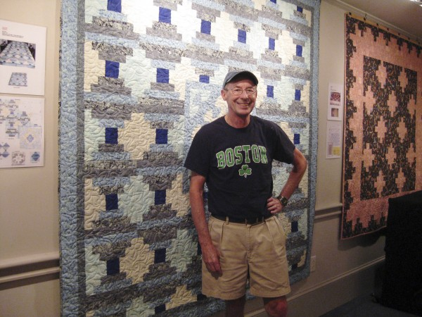 "Quilter Jacque Huber stands in front of his ""Sea Foam"" quilt, one of many on display through Sept. 27 at the Camden Public LIbrary."