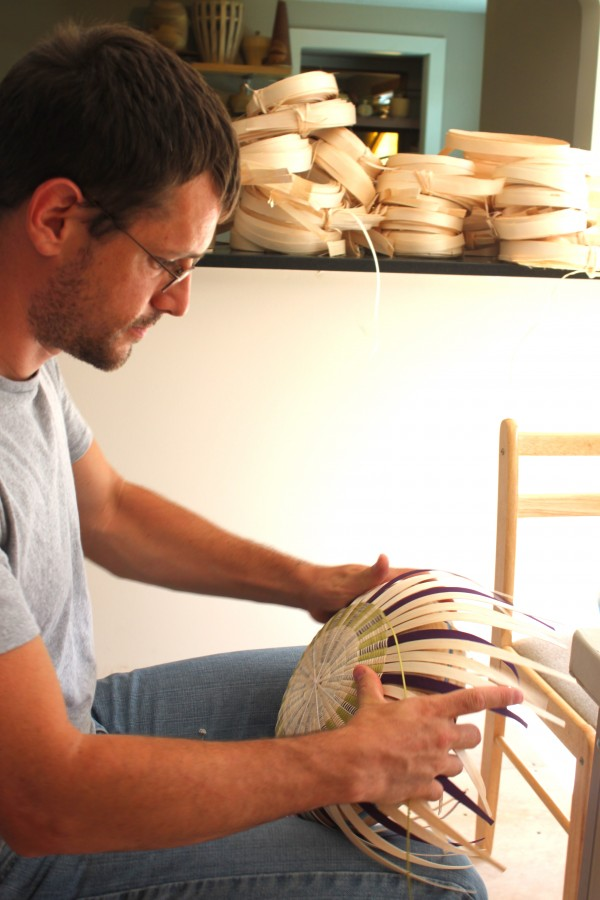 "Passamaquoddy basketmaker Jeremy Frey weaves the bottom of an ash basket Tuesday at his studio in the Indian Township of Princeton. The basket is a traditional form, modeled after sea urchins. Frey was recognized nationally at the Santa Fe Indian Market in August when he won ""Best of Show."""