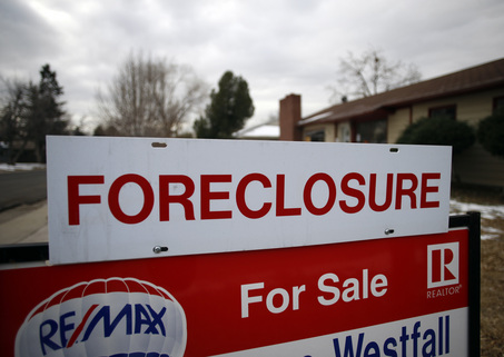 A foreclosure sign sits on top of a sale placard outside an home on the market in the south Denver suburb of Littleton, Colo.