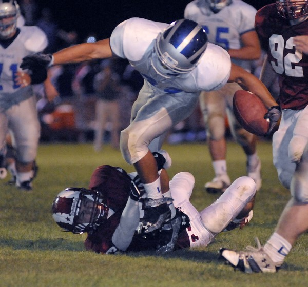 Lawrence running back Shawun Caroll (32) slips the grasp of Bangor's Nick Sherwood (83) and runs for a touchdown in the second half of their game in Bangor Saturday night, Sept. 10, 2011. Lawrence won 32-25.