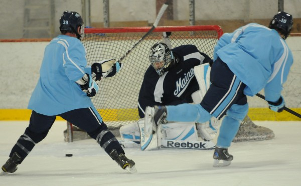 University of Maine hockey players Joey Diamond (left) and Brian Flynn (right) converge on goalie Josh Seeley after Seeley makes a save during a recent captain's practice at Brewer's Penobscot Ice Arena. The Bears were practicing in Brewer while Alfond Arena was being renovated.