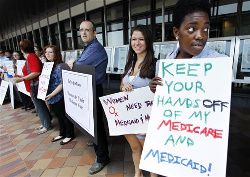 Dena Robinson, from right, and Hannah Hoffman, join dozens of Medicare advocates gathered outside the Newseum in Washington. Democrats are hitting the reset button on health care for next year's elections. Weary of getting pounded over the new health overhaul law, President Barack Obama and his party are changing the subject to Medicare.