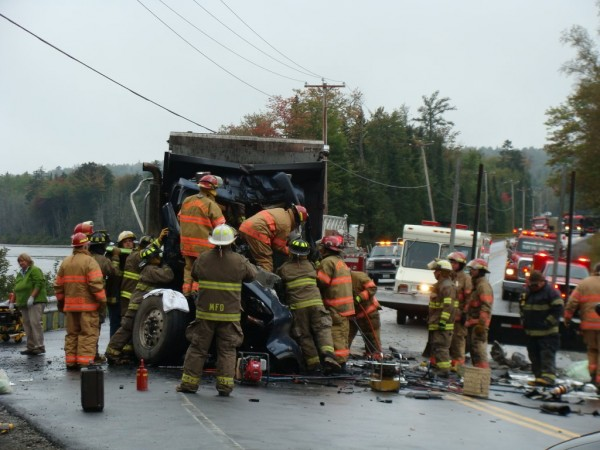 Greenville, Monson and Guilford rescue officials work to free the driver of a dump truck that collided with a tractor-trailer truck at about 12:30 p.m. Thursday at the sharp curve at Spectacle Pond in Monson.