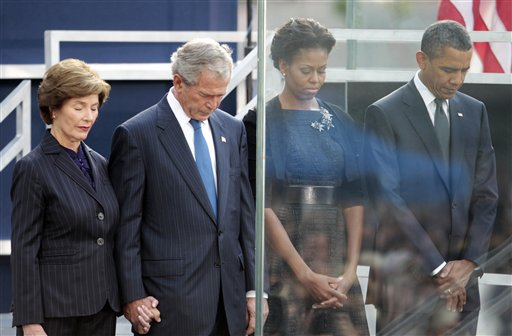 President Barack Obama and first lady Michelle Obama, former President George W. Bush and former first lady Laura Bush bow their heads during a moment of silence at Ground Zero in New York, Sunday, Sept., 11, 2011 in New York.