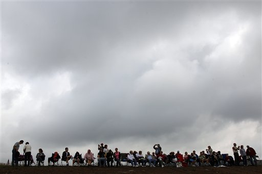 People gather on a hilltop overlooking phase I of the permanent Flight 93 National Memorial before its dedication near the crash site of Flight 93 in Shanksville, Pa. Saturday Sept. 10, 2011.