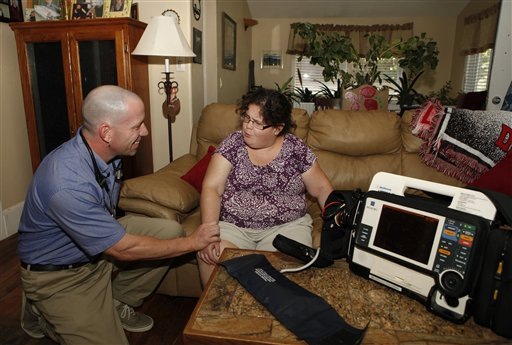 In this Aug. 31, 2011 photo, Eagle County paramedic Kevin Creek checks the pulse of Danielle Hefferan, 21, during a house call at her home  in Eagle, Colo. As part of a pilot project, Creek now spends his days making house calls to take electrocardiograms, check patient prescriptions, check blood pressure, draw blood and make other observations that used to require a doctor's visit.