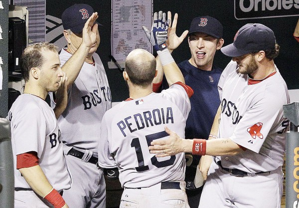 Boston Red Sox teammates congratulate Dustin Pedroia in the dugout after he hit a solo home run in the fifth inning of Wednesday night's game in Baltimore against the Orioles. Baltimore scored twice in the bottom of the ninth to earn a 4-3 victory.