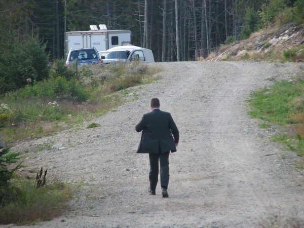 Lt. Chris Coleman of the Maine State Police walks down a dirt road Friday at the Ocean's End development in Southwest Harbor during a search for clues about remains found on the property on Aug. 25. Maine State Police said Friday that the remains are likely those of missing local resident Pete Peterson.