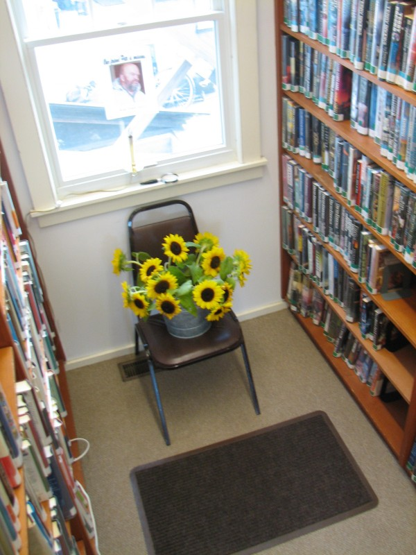 A pail of sunflowers sit Friday in a chair that Pete Peterson used to like to sit in at the Southwest Harbor Public Library.