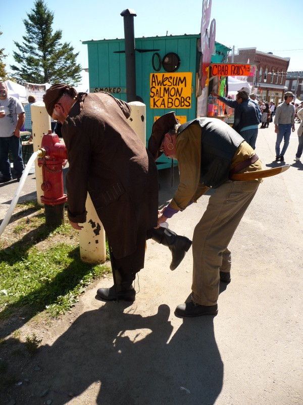 "Peter Gould, 68, ties the pirate boot of Jim Mofitt, 64, at the Eastport Pirate Festival Saturday. Both men are from Baileyville and said they have attended the festival all three years. ""It gives us a chance to be a kid again for one day,"" Gould said."