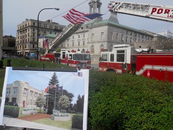 An architect's rendering of a memorial to Portland firefighters who died in the line of duty stands in front of two ladder trucks hoisting the American flag Friday at the memorial's groundbreaking.
