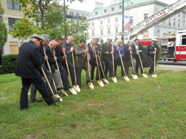 Sponsors, dignitaries and Portland Fire Department officers conduct the ceremonial groundbreaking for a new memorial near the Congress Street fire station Friday morning. The memorial will honor Portland firefighters who died in the line of duty.