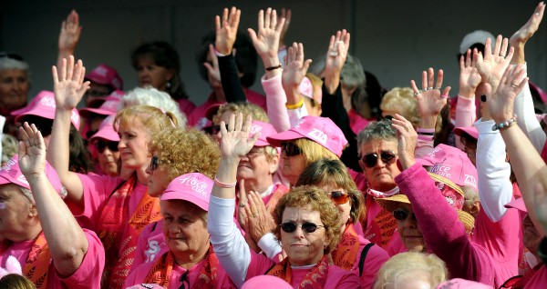 Breast cancer survivors acknowledge cheers from the crowd before the start of the 15th annual Susan G. Komen Race for the Cure in Bangor Sunday morning. More than 5000 people participated in the event that raises money for breast cancer research.