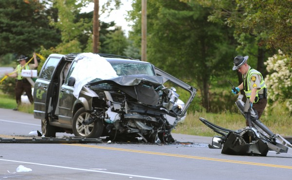 Penobscot Sheriff Deputy William Birch pulls debris from the ditch and piles it next to one of two vans that were involved in a head-on collision on Route 9 in Eddington on Thursday, September 1, 2011.