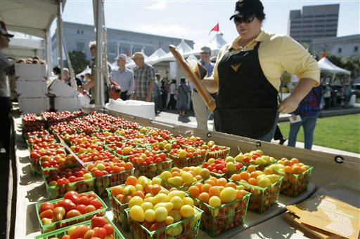 "Benina Burroughs of Merced, Calif. looks over a display of cherry tomatoes  at a farmer's market during the 2008 Slow Food Nation celebration  in San Francisco. Can you eat well without being wealthy? That's the focus of a $5 meal challenge being launched this month by Slow Food USA. The object is to get people to commit to making a ""slow food"" meal, using whole ingredients rather than processed foods, for $5 per person or less."