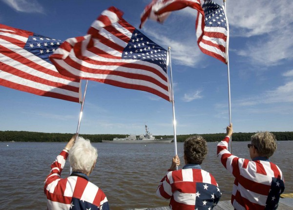 JoAnn Miller, left, Carmen Footer, center, and Elaine Greene — better known as the Freeport Flag Ladies — wave Old Glory from a dock at the Maine Maritime Museum in Bath as the USS Spruance departs Bath Iron Works and slips down the Kennebec River to the sea Thursday.