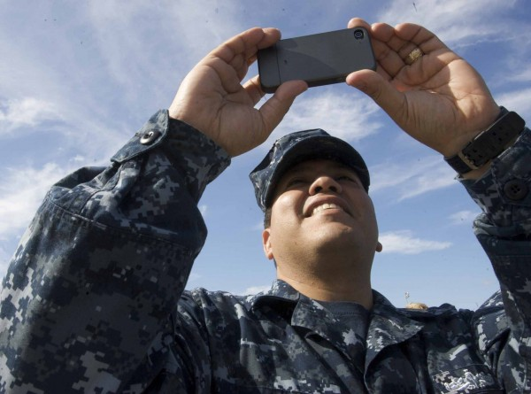 Jesse Garcia, quartermaster chief of the unfinished destroyer Michael Murphy, takes a video with his phone as the USS Spruance departs Bath Iron Works and makes its way down the Kennebec River to the sea Thursday.