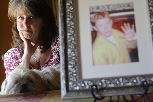 Cheryl Morin and her dog Tiny sit near a family photo of her son, Joe Day, then 16. Day took his life in November 2005 when he was 19 years old. Morin established the JD Foundation to heighten suicide awareness and prevention.